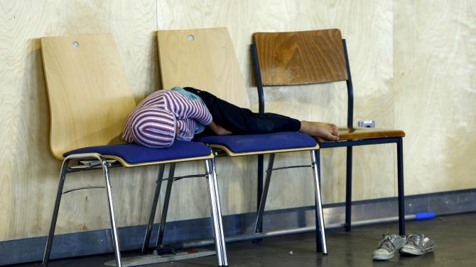 A child sleeps on three chairs as asylum seekers wait to be registered inside a hall, used by German police as the first registration point, in Passau