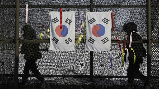 South Korean army soldiers patrol by the national flags and ribbons, wishing for the reunification of the two Koreas, attached on the barbed-wire fence at the Imjingak Pavilion near the border village of Panmunjom, which has separated the two Koreas since the Korean War, in Paju, north of Seoul, South Korea, Wednesday, Feb. 13, 2013. Defying U.N. warnings, North Korea on Tuesday conducted its third nuclear test in the remote, snowy northeast, taking a crucial step toward its goal of building a bomb small enough to be fitted on a missile capable of striking the United States. (AP Photo/Lee Jin-man)