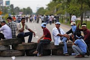 Rubber farmers sit on tyres as they block a road during a protest in Surat Thani