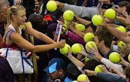 Russia's Maria Sharapova signs autographs following her victory over Israel's Shahar Peer during their women's singles tennis first round match at the All England Tennis Club in Wimbledon, southwest London, during the London 2012 Olympic Games
