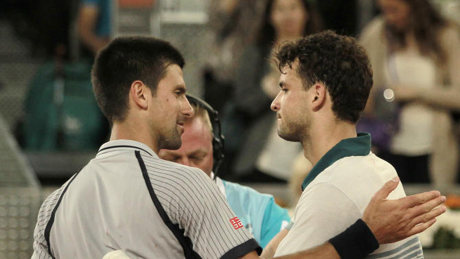 Novak Djokovic from Serbia, left, hugs Grigor Dimitrov from Russia, right, during the Madrid Open tennis tournament, in Madrid, Tuesday, May 7, 2013. (AP Photo/Andres Kudacki)