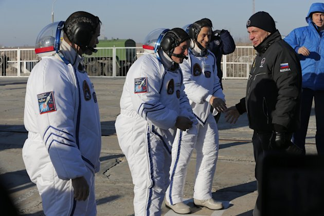 Russia's Space Agency Chief Vladimir Popovkin greets U.S. astronaut Thomas Marshburn, right, Russian cosmonaut Roman Romanenko, center, and Canadian astronaut Chris Hadfield, crew members of the missi