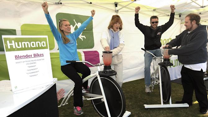 IMAGE DISTRIBUTED FOR HUMANA- Jessica Walke, 29, of Indio, and husband Russell Walke, 32, celebrate as they finish a turn on Humana smoothie bikes during Humana Day at Certified Farmers' Market in Old Town La Quinta on Sunday, Jan. 13, 2013 in La Quinta, Calif. Patrons enjoyed fresh food, music and a culinary demonstration from regionally based vendors. The Farmers' Market event was one of many wellness-focused activities taking place leading up to the 2013 Humana Challenge PGA TOUR golf tournament, which will be held Jan. 14-20, 2013, in La Quinta, Calif.† (Rodrigo Pena / AP Images for Humana).