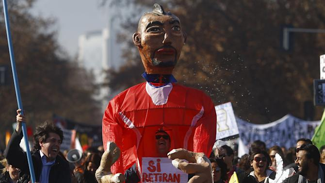A protester holds a giant figurine that represents Chile's Vidal, as teachers march during a demonstration to demand changes in the Chilean education system in Santiago