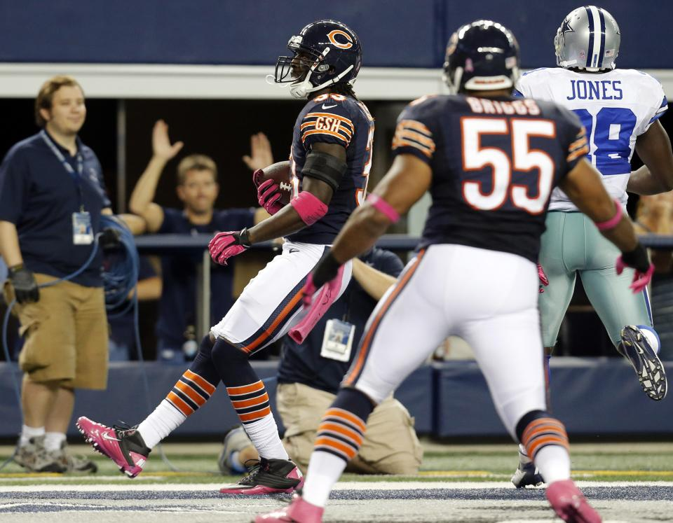Chicago Bears cornerback Charles Tillman returns an interception for a touchdown past Dallas Cowboys running back Felix Jones (28) as Bears' Lance Briggs (55) watches during the first half of an NFL football game, Monday, Oct. 1, 2012, in Arlington, Texas. (AP Photo/Sharon Ellman)
