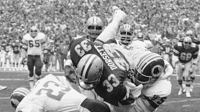 FILE - In this Jan. 22, 1983, file photo, Dallas Cowboys Tony Dorsett takes a hard hit and fumbles the ball in first quarter of an NFL football game against the Washington Redskins in Washington. Dorsett is one of at least 300 former players suing the National Football League, claiming the NFL pressured them to play with concussions and other injuries and then failed to help them pay for health care in retirement to deal with those injuries. (AP Photo/File)