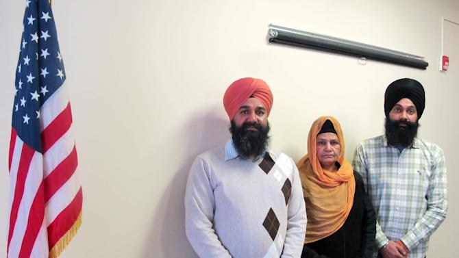 In this Jan 16, 2013 photo, Kulwant Kaur, wife of Punjab Singh, poses with her sons Raghuvinder Singh, left, and Jaspreet Singh in a conference room at the long-term care facility in Wisconsin where Punjab Singh is recovering. Punjab was critically injured in a shooting rampage at a Sikh temple in Oak Creek, Wis., in August 2012, that left six people dead. Kulwant and her sons watched over the 65-year-old Sikh priest 24 hours a day at the facility where he remained largely unresponsive until January 2013, when he began showing signs of cognitive improvement. (AP Photo/Dinesh Ramde)