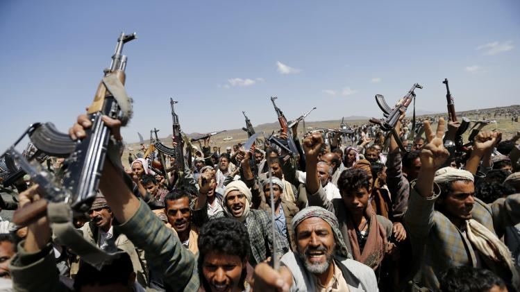 Followers of the Shi'ite Houthi group brandish their weapons during a gathering near Sanaa