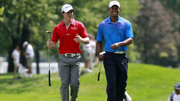Rory McIlroy (L) talks with Tiger Woods