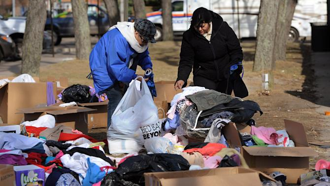 Two women look through piles of clothing in front of Long Beach city hall donated for victims of Superstorm Sandy on Tuesday, Nov 6, 2012, in Long Beach, N.Y. (AP Photo/Kathy Kmonicek)