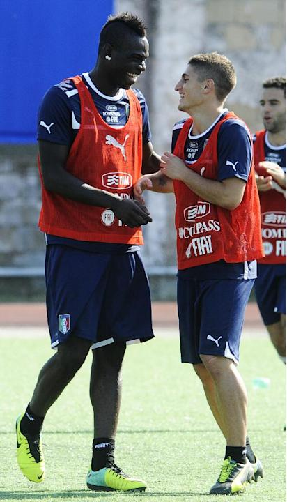 Italy's Mario Balotelli sheres a light moment with Alessandro Florenzi, right, during a training session with their team at the Giarrusso stadium in the outskirts of Naples, Monday, Oct. 14, 2013, ahe