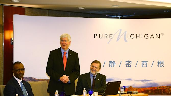 This photo released by the office of Michigan Gov. Rick Snyder shows Snyder, center, in Shanghai, China, on Tuesday, Nov. 25, 2014, during his trade mission to China. Snyder is shown talking with travel reporters at a meeting to promote Chinese tourism in Michigan. He is flanked by Mike Finney, left, chief executive of the Michigan Economic Development Corp., and Dave Lorenz, manager of industry relations for Travel Michigan. (AP Photo/Office of Michigan Gov. Rick Snyder)