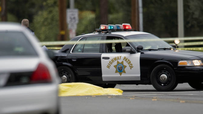 A body lays in the intersection of Wanda Road and Katella Avenue early Tuesday, Feb. 19, 2013 in Orange County, Calif.,  as local police agencies investigate the scene.  Police say a chaotic 25-minute shooting spree through Orange County left a trail of dead and injured victims before the shooter killed himself. Orange County sheriff's spokesman Jim Amormino say there are at least six crime scenes with three people, including the suspected gunman, dead and several others wounded. Tustin police Supervisor Dave Kanoti said the shootings started with an apparent carjacking just after 5 a.m. Tuesday in an unincorporated Ladera Ranch area of Orange County. (AP Photo/The Orange County Register, Mark Rightmire)   MAGS OUT; LOS ANGELES TIMES OUT