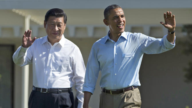 FILE - In this Saturday, June 8, 2013 file photo, President Barack Obama, right, and Chinese President Xi Jinping wave as they walk at the Annenberg Retreat of the Sunnylands estate in Rancho Mirage, Calif. Weekend revelations that an American whistleblower holed up in Hong Kong has given an early test to the new working relationship the presidents of the U.S. and China tried to forge just a day earlier. (AP Photo/Evan Vucci, File)