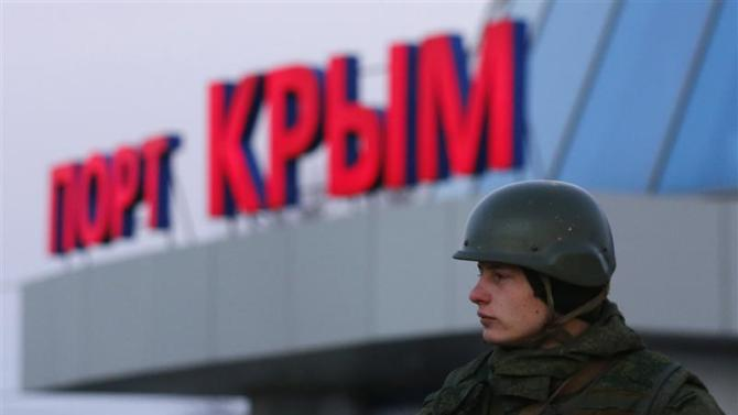 An armed man, believed to be a Russian soldier, stands outside the civilian port in the Crimean town of Kerch