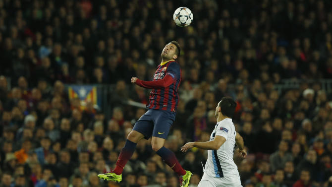 Barcelona's Jordi Alba, left jumps above Manchester City's Sergio Aguero during a Champions League, round of 16, second leg, soccer match between FC Barcelona and Manchester City at the Camp Nou Stadium in Barcelona, Spain, Wednesday March 12, 2014. (AP Photo/Emilio Morenatti)