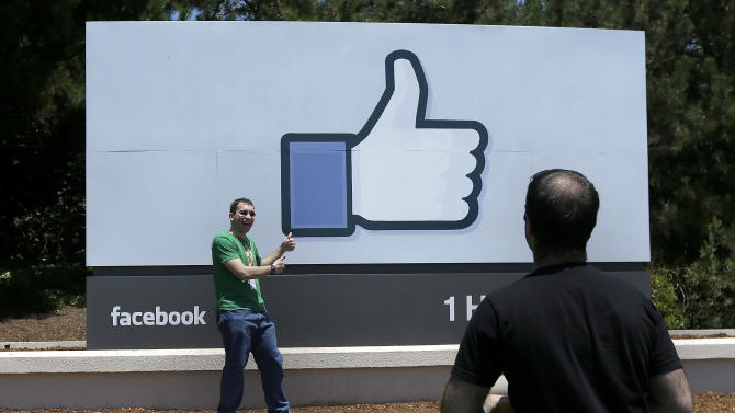 FILE - In this June 11, 2014, file photo, a man poses for photographs in front of the Facebook sign on the Facebook campus in Menlo Park, Calif. Facebook reports quarterly financial results on Wednesday, July 29, 2015. (AP Photo/Jeff Chiu, File)