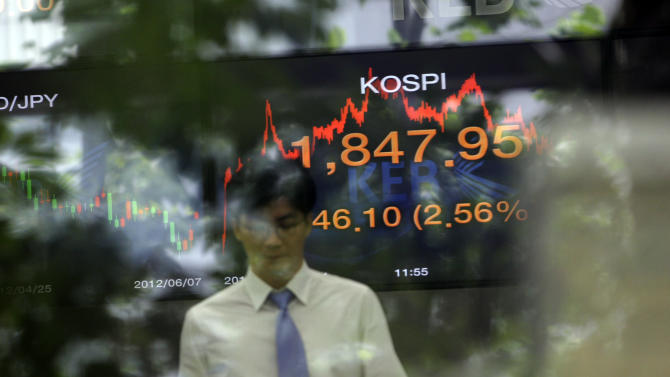 A currency trader and a monitor showing KOSPI are seen through a window at the foreign exchange dealing room of the Korea Exchange Bank headquarters in Seoul, South Korea, Thursday, June 7, 2012. South Korea's Kospi rose 2.56 percent, or 46.10 points, to close at 1,847.95. (AP Photo/Lee Jin-man)