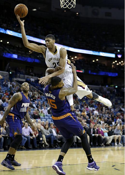 New Orleans Pelicans power forward Anthony Davis (23) is fouled by Phoenix Suns power forward Marcus Morris (15) as he drives to the basket in the second half of an NBA basketball game in New Orleans,