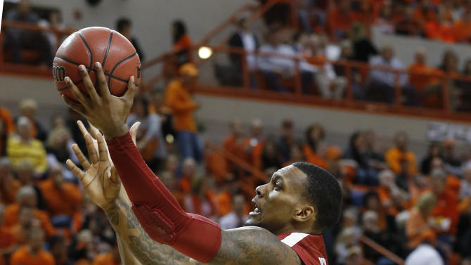 Oklahoma forward Romero Osby (24) goes up for a shot in front of Oklahoma State forward Michael Cobbins (20) in the second half of an NCAA college basketball game in Stillwater, Okla., Saturday, Feb. 16, 2013. Oklahoma State won 84-79. (AP Photo/Sue Ogrocki)