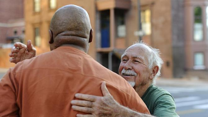 In this Wednesday, May 1, 2013 photo, haircut client Danny Thomas, left, hugs Anthony Cymerys, known as Joe the Barber, after his haircut in Hartford, Conn. For more than 20 years, Cymerys has been cutting hair alfresco in Hartford for the fee of a hug. (AP Photo/Jessica Hill)