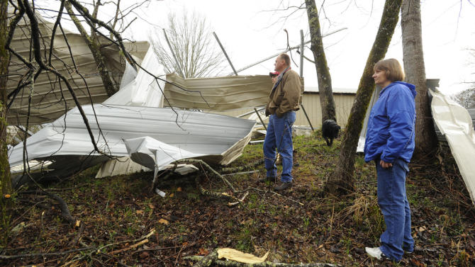 David McCullars, wife Kay and son David Jr. survey the damage to their 36x48x16 RV shed destroyed by high winds on Ridgetop Lane in Clay, Ala., Monday, March 18, 2013. A severe line of thunderstorms moved through central Alabama just after 3:30 p.m. snapping trees and knocking out power making travel hazardous. Trees fell on power lines  that crossed the road on Old Springville Road and Clayton Road. (AP Photo/AL.com, Joe Songer)