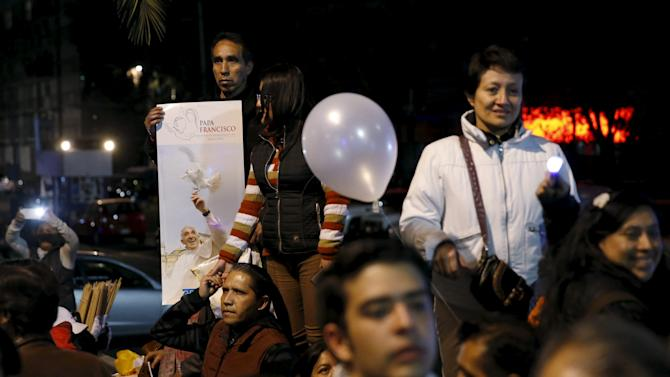 People stand along a street as they wait for Pope Francis to drive past in Mexico City