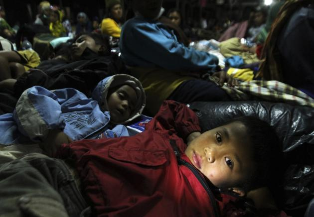 A child refugee lies down at temporary shelter with his family and other villagers. More than 1,500 people have been evacuated from the danger. (Reuters)