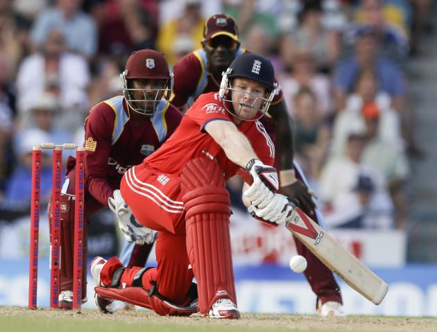 England's Eoin Morgan hits a four off West Indies' Sunil Narine during their first T20 International cricket match at the Kensington Oval in Bridgetown, Barbados, Sunday, March 9, 2014. (AP Ph