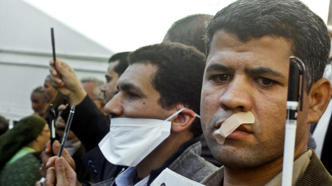 "Egyptian journalists tape their mouths and raise their pens during a demonstration against the draft constitution in Cairo, Egypt, Sunday, Dec. 23, 2012. Egypt's opposition called Sunday for an investigation into allegations of vote fraud in the referendum on a deeply divisive Islamist-backed constitution after the Muslim Brotherhood, the main group backing the charter, claimed it passed with a 64 percent ""yes"" vote. Official results have not been released yet and are expected on Monday. (AP Photo/Amr Nabil)"