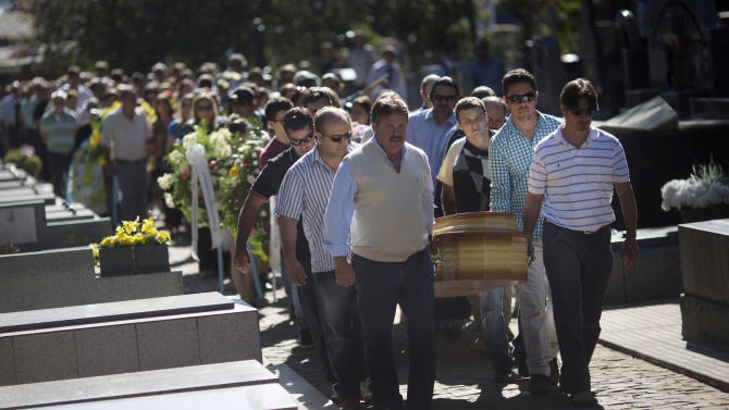 Relatives and friends carry the coffins of two brothers, Pedro and Marcelo Salla, who died in a nightclub fire, as they prepare to bury them at a cemetery in Santa Maria, Brazil, Monday, Jan. 28, 2013. A fast-moving fire roared through the crowded, windowless Kiss nightclub in this southern Brazilian city early Sunday, killing more than 230 people. Many of the victims were under 20 years old, including some minors. (AP Photo/Felipe Dana)