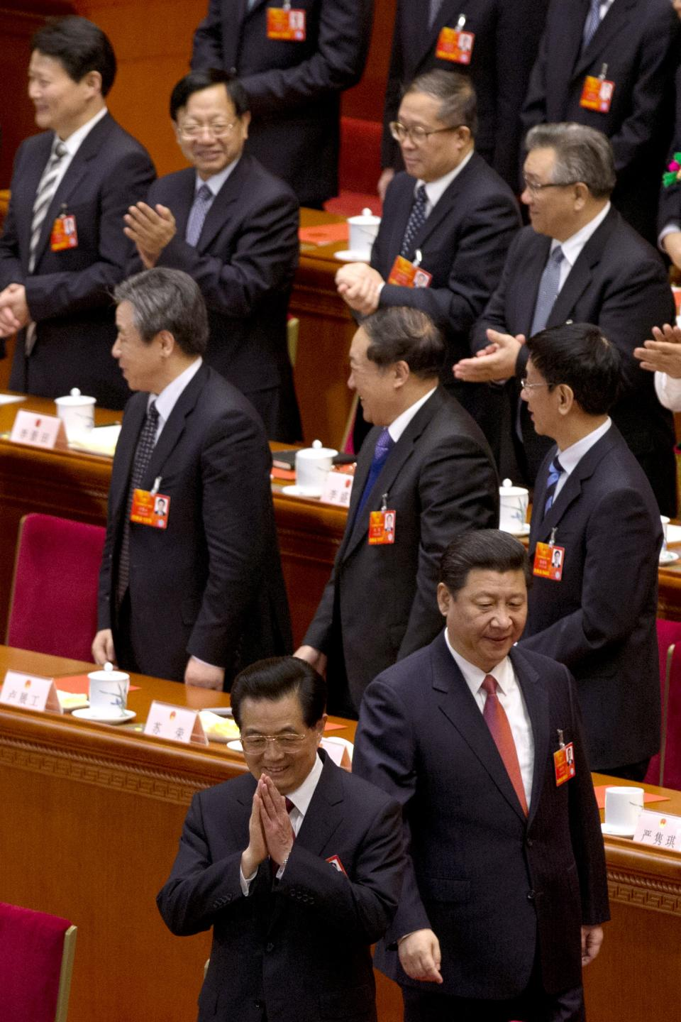 Outgoing Chinese President Hu Jintao, bottom center, gestures near Chinese Communist Party chief and incoming-President Xi Jinping at right as they attend a plenary session of the National People's Congress where delegates are expected to elect Xi officially as president at the Great Hall of the People in Beijing Thursday, March 14, 2013. (AP Photo/Ng Han Guan)