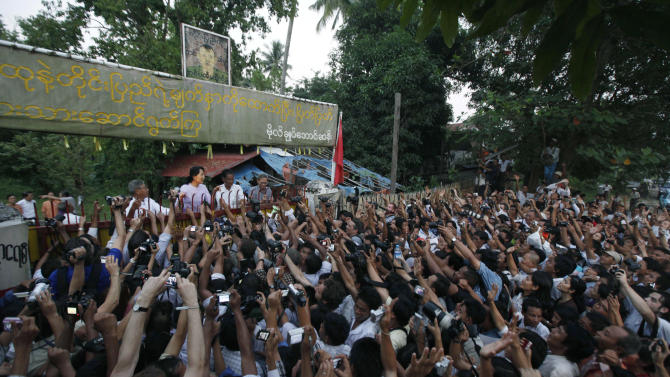 "FILE - In this Nov. 13, 2010 file photo, Myanmar's pro-democracy leader Aung San Suu Kyi, rear, addresses her supporters from her house compound after her release from house arrest in Yangon, Myanmar. President Barack Obama's historic visit to Myanmar on Monday, Nov. 19, 2012 is meant to show America's support for the country's transition to democracy. The White House has cautioned that Obama's trip to the former pariah state should not be viewed as a ""victory celebration"" but as an opportunity to press for urgent action still needed in Myanmar. Notably, freeing political prisoners and ending ethnic tension in remote areas. (AP Photo/File)"