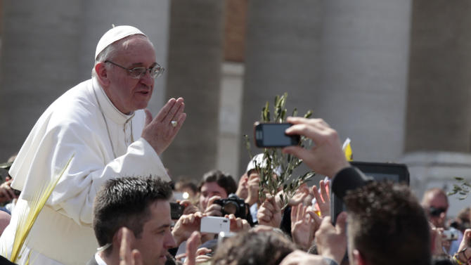 Pope Francis blows a kiss to faithful after celebrating his first Palm Sunday Mass in St. Peter's Square at the Vatican, Sunday, March 24, 2013. Pope Francis celebrated his first Palm Sunday Mass in St. Peter's Square, encouraging people to be humble and young at heart, as tens of thousands joyfully waved olive branches and palm fronds.The square overflowed with some 250,000 pilgrims, tourists and Romans eager to join the new pope at the start of solemn Holy Week ceremonies, which lead up to Easter, Christianity's most important day. (AP Photo/Gregorio Borgia)