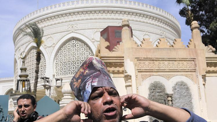 "A member of Egypt's April 6 Youth Movement shouts anti-Muslim brotherhood slogans as he wears a hat with pictures of victims of recent clashes with Arabic reading, ""the Brotherhood's terrorism"", in front of the presidential palace in Cairo, Egypt, Saturday, April 6, 2013. The group is rallying Saturday to mark its fifth anniversary and to protest against President Mohammed Morsi.  (AP Photo/ Amr Nabil)"