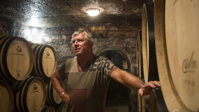 "In this Sept. 10, 2012 photo, Jean-Michel Guillon, owner of the Domaine Guillon, stands in his cellar Gevrey-Chambertin in Burgundy, Eastern France in Burgundy, Eastern France. Guillon, who led a local bid to buy the thousand-year-old Chateau de Gevrey-Chambertin, says a state agency valued the estate at 3.5 million euros. His group first offered 4 million euros, then 5 million, but the Masson family, which has owned the estate for more than 150 years, refused. ""They said, 'We want more, we want a million each,'"" Guillon says. (AP Photo/Laurent Cipriani)"