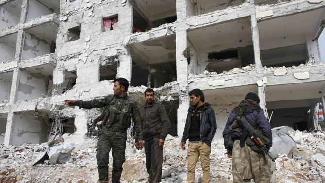 Fighters of the Kurdish People's Protection Units (YPG) stand on the debris of a damaged building in the streets in the northern Syrian town of Kobani