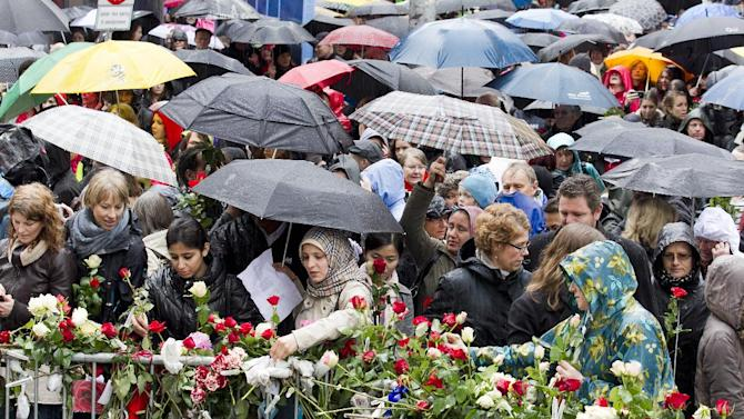 "People lays flowers  near the entrance  the courthouse in Oslo where  Anders Behring Breivik  is standing trial Thursday April 26, 2012. Nearly  40,000 people who turned up in poor weather at the Youngstorget Square in Oslo  to participate in the singing of ""Barn av Regnbuen""  ""Children of the Rainbow"" . The song which was a hit of Norwegian folk singer Lillebjoern Nilsen several decades ago, has become a signature tune for the victims of the July 22, 2011 bombing and shooting massacre that killed 77 people. (AP Photo/Heiko Junge / NTB scanpix) NORWAY OUT"