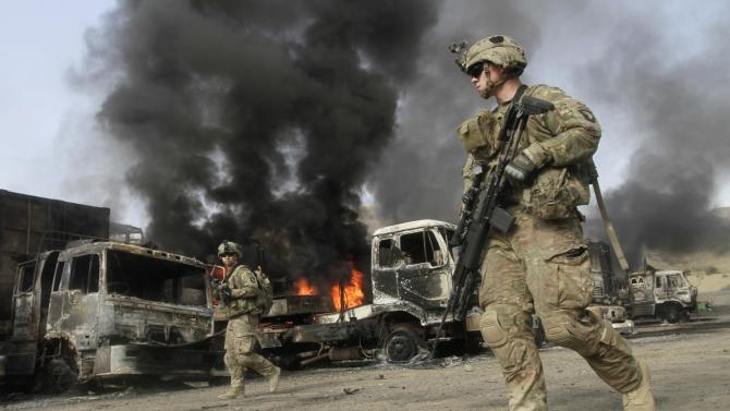 NATO troops walk near burning NATO supply trucks after, what police officials say, was an attack by militants in the Torkham area