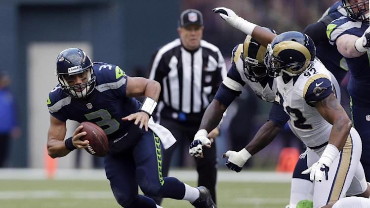Seattle Seahawks quarterback Russell Wilson (3) scrambles away from St. Louis Rams' Eugene Sims, right, and William Hayes, second from right, in the first half of an NFL football game against the St. Louis Rams, Sunday, Dec. 30, 2012, in Seattle. (AP Photo/Elaine Thompson)