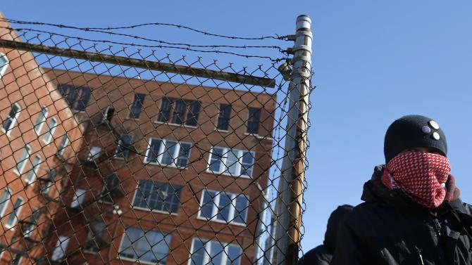 A protestor stands outside a police facility called Homan Square, demanding an investigation into a media report denied by police that the site functions as an off-the-books interrogation compound, in Chicago