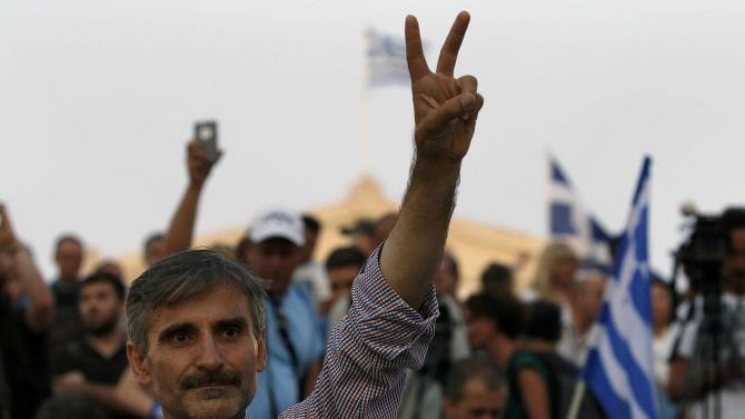 "A ""No"" supporter flashes victory sign following referendum results in Athens"