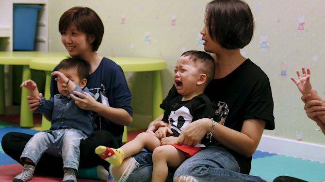 A child cries in the arms of his mother as they participate in a specialized class preparing toddlers for kindergarten interviews in Hong Kong