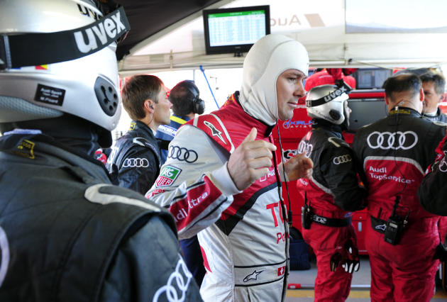 Audi Sport driver Marcel Fassler, center, of Switzerland, stretches before warmup for the American Le Mans Series' Petit Le Mans auto race at Road Atlanta, Saturday, Oct. 1, 2011, in Braselton, Ga.  (