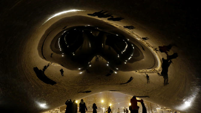 People enjoy a snow-covered Cloud Gate at Millennium Park in downtown Chicago, which became a great photo opportunity for visitors, Wednesday, Jan. 1, 2014. As much as 9 inches of snow has fallen in some parts of the Chicago area since New Year's Eve, and a second wave is expected to dump several more inches by Thursday. (AP Photo/Nam Y. Huh)