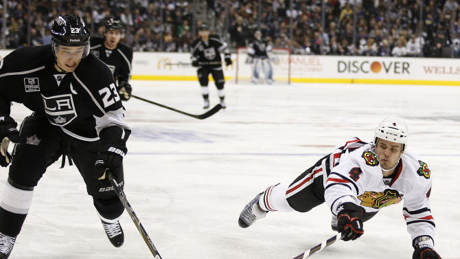 Los Angeles Kings' Dustin Brown, left, and Chicago Blackhawks' Niklas Hjalmarsson, of Sweden, reach for the puck during the second period of an NHL hockey game in Los Angeles, Saturday, Jan. 19, 2013. (AP Photo/Jae C. Hong)