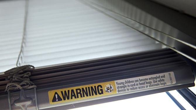 A label warns of strangulation risks from mini blind cords as seen on Wednesday, May 6, 2015, in Washington. The industry launched a campaign that encourages companies to send their products to a third-party testing facility to determine whether they should be used in homes with little ones. (AP Photo/Jacquelyn Martin)