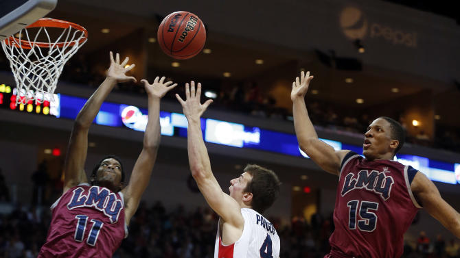 Gonzaga's Kevin Pangos, of Canada, center, shoots while covered by Loyola Marymount's Nick Stover, left, and Alex Osborne, right, during the second half of a West Coast Conference tournament NCAA college basketball game on Saturday, March 9, 2013, in Las Vegas. Gonzaga defeated Loyola Marymount 66-48. (AP Photo/Isaac Brekken)