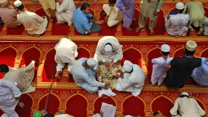 In this Friday, Aug. 17, 2012 photo, Pakistani men, center, count money they collected for worshippers to be delivered to poor families, on the last Friday of the Muslim holy fasting month of Ramadan, in a mosque in Gujranwala, Pakistan. For many years, Pakistan required all Sunni Muslims, who make up a majority of the country's population, to pay zakat to the government. That regulation changed recently, but many Pakistanis seem unaware and continue to pull their money out of the bank to elude the state. (AP Photo/Aftab Rizvi)