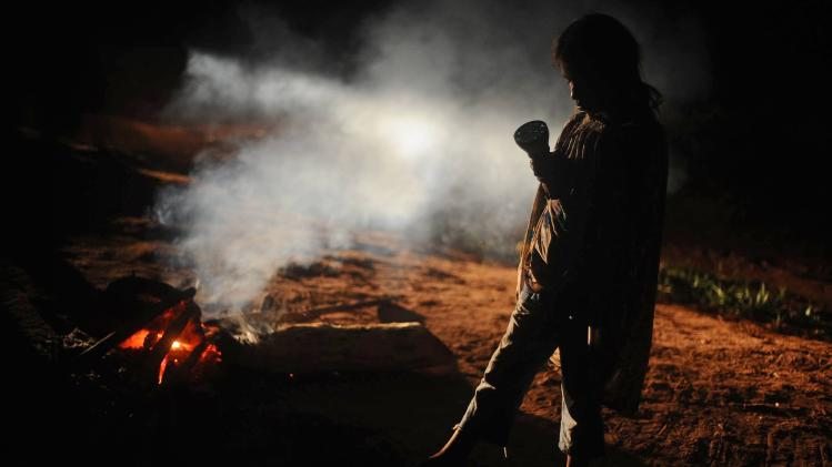 A member of the Guarani Nandeva tribe performs a ritual of war and protection on the 78th day of their occupation of 14 farms they claim are part of the ancestral land they call Tekoha Yvy Katu